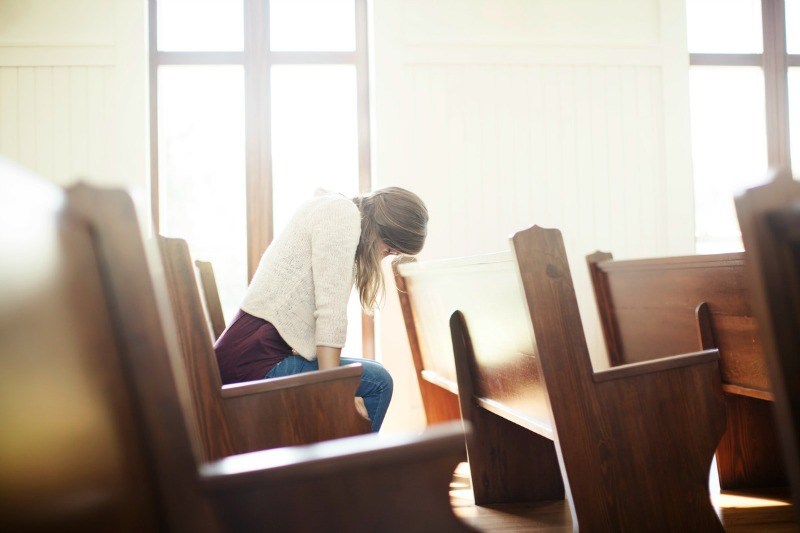 Woman in pew praying (800)
